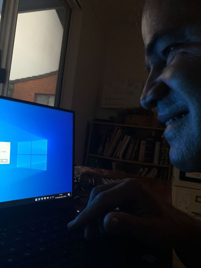 Adam using Jaws - Adam typing at his laptop using jaws with a blue screen lighting up his smiling face